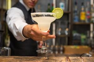 A bartender holds out a margarita